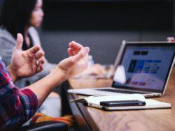 Personer diskuterer rundt bord med laptop