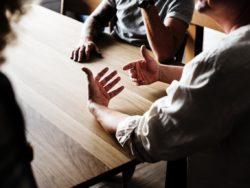 Personer som sitter rundt et bord og snakker