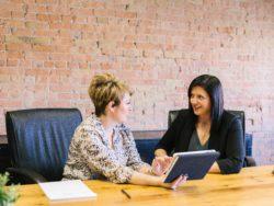 To kvinner snakker sammen og ser på nettbrett