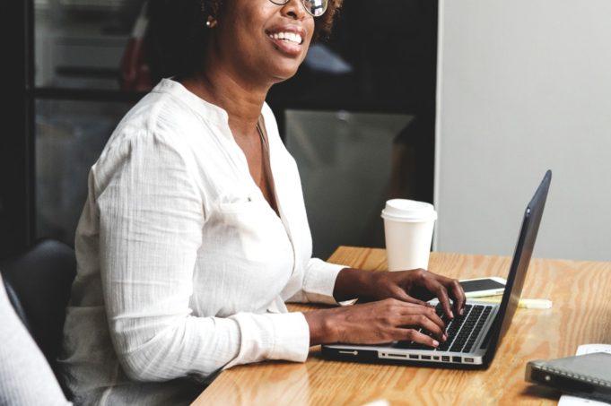 Person skriver på laptop i møte