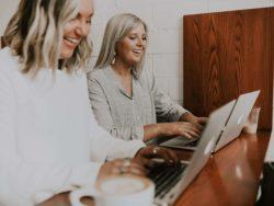 To personer bruker laptop og smiler