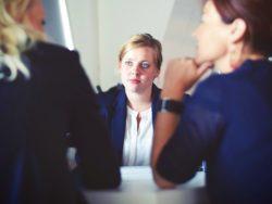 En person snakker med to personer sett bakfra