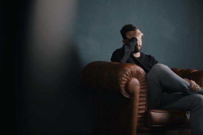 Person sitter i sofa med hånden foran ansiktet