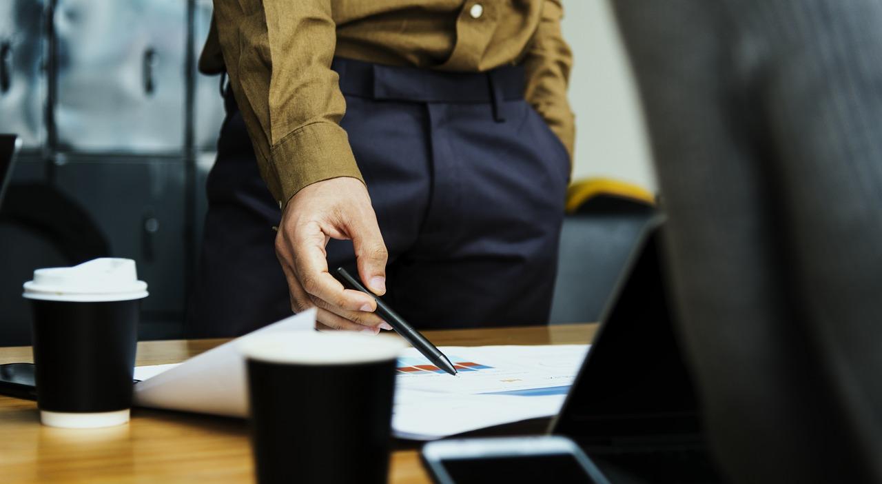 Person holder penn og peker på papirer