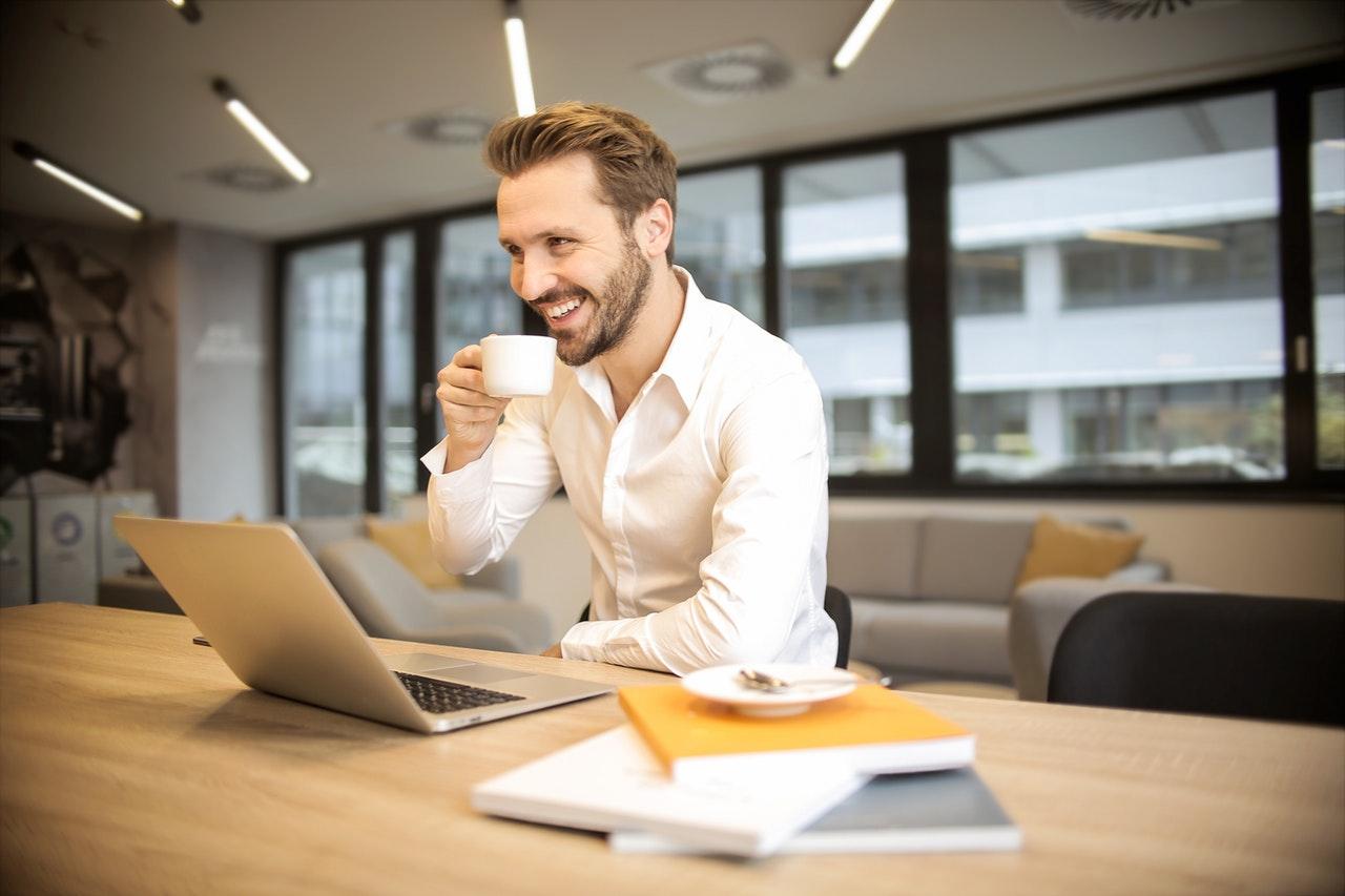 Mann drikker kaffe og smiler