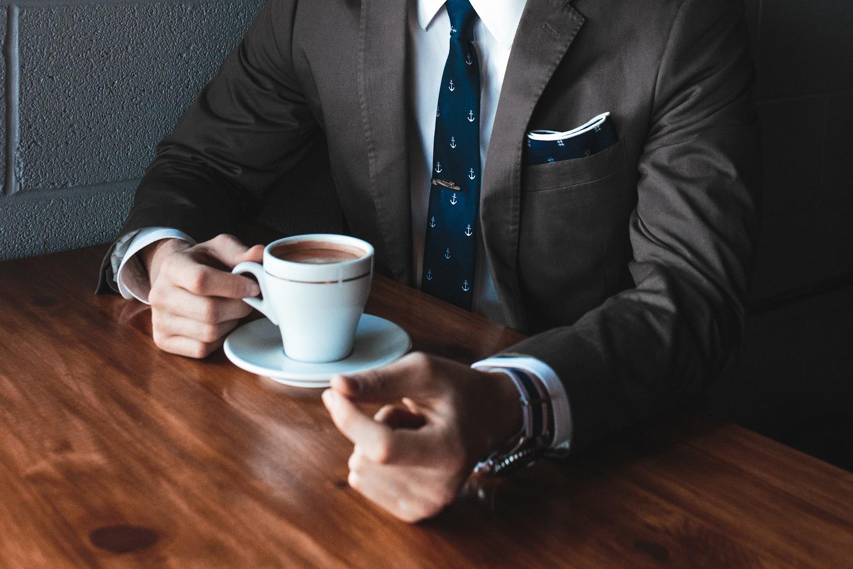 Person drikker kaffe ved et bord