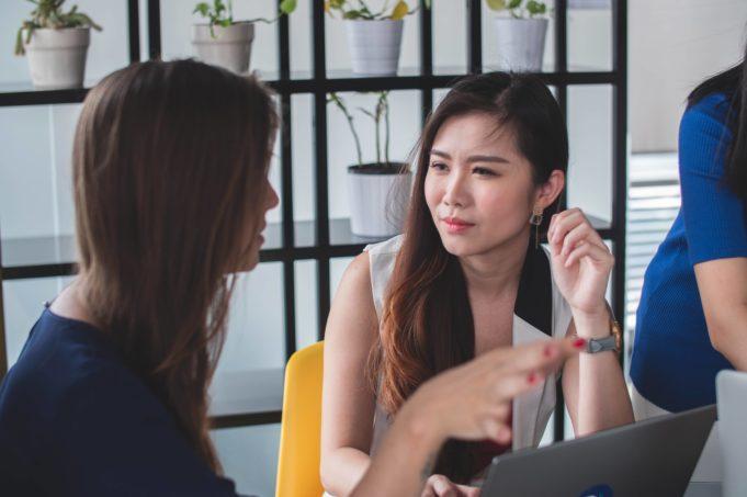 To kvinner prater foran laptop