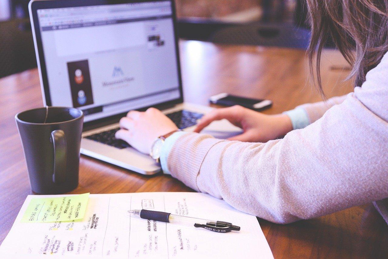 fotografi av kvinne som jobber med laptop og skriveblokk