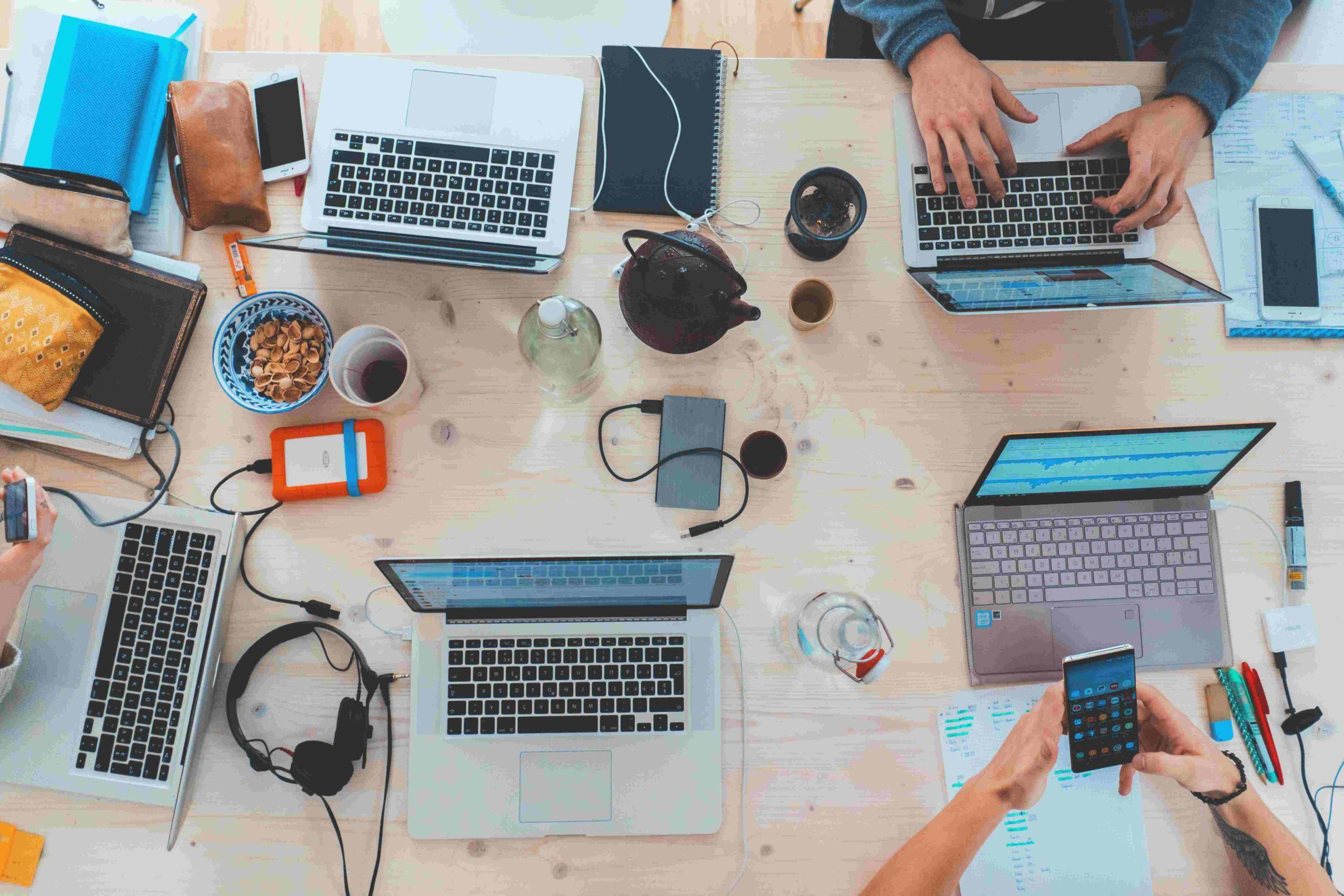 Fotografi av et bord med mange datamaskiner og folk som jobber