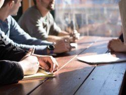 Bilde av mennesker som sitter samlet rundt et bord