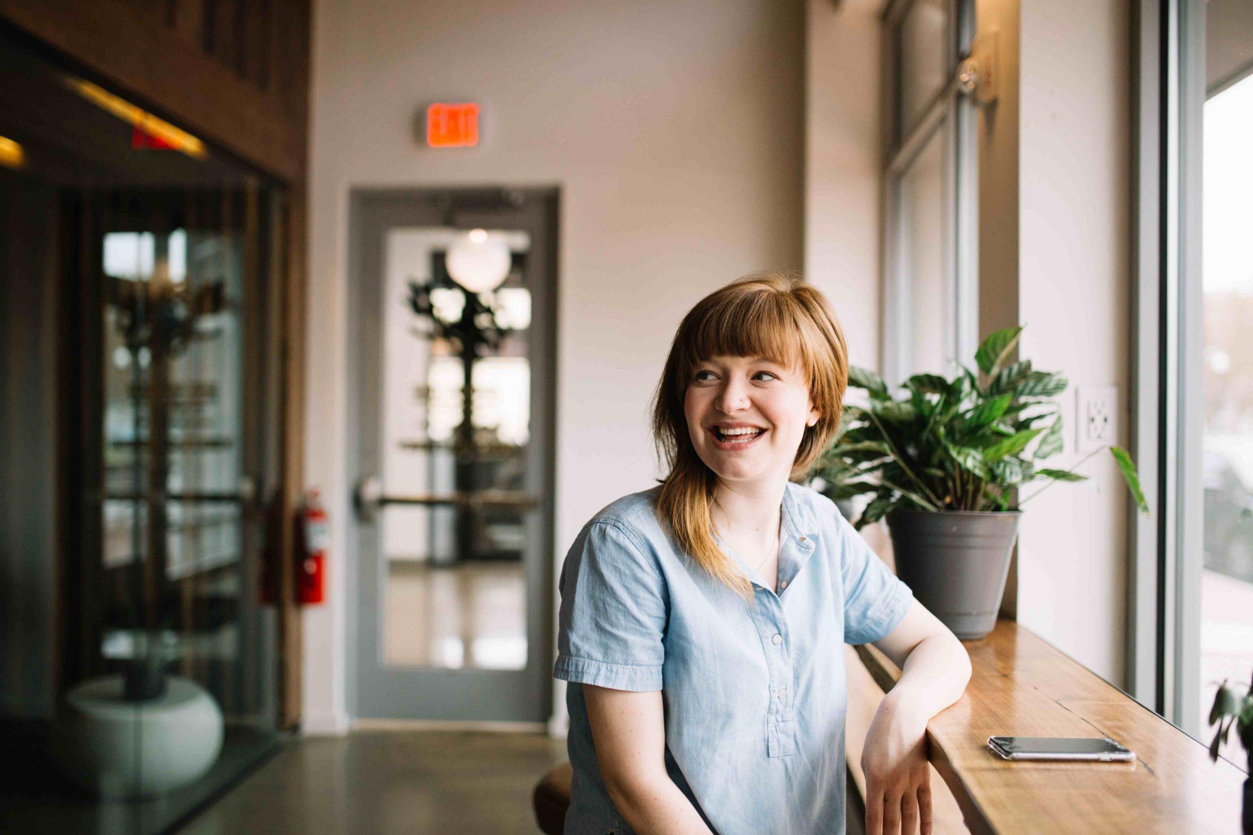 Fotografi av rødhåret kvinne som sitter ved vinduet