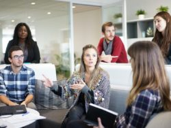 Fotografi av seks unge mennesker på en arbeidsplass